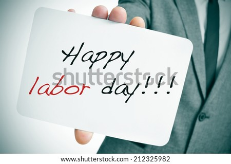 a man wearing a suit showing a signboard with the text happy labor day written in it - stock photo