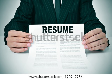a man wearing a suit showing his resume - stock photo