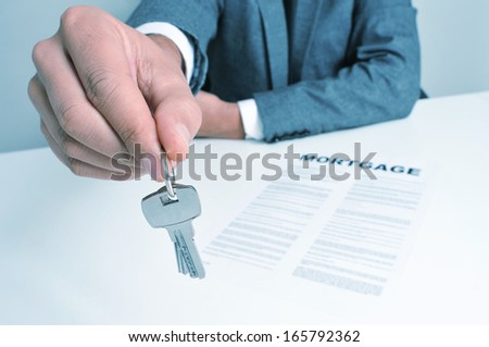 a man wearing a suit sitting in a desk with a mortgage contract giving a key ring to the observer - stock photo
