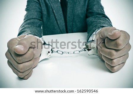 a man wearing a suit sitting in a desk, with handcuffs in his wrists - stock photo