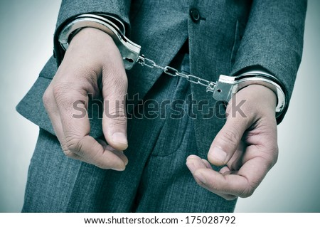 a man wearing a suit with handcuffs in his wrists - stock photo