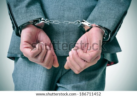 a man wearing a suit with his wrists handcuffed in the back - stock photo