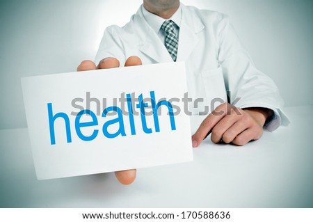 a man wearing a white coat showing a signboard with the word health written in it - stock photo