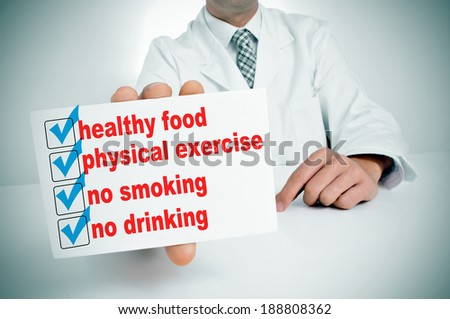 a man wearing a white coat sitting in a desk showing a signboard with some healthy habits, such as healthy food, physical exercise or no smoking - stock photo