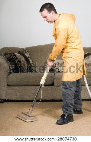 A man wearing a work coat and vacuuming the carpets inside a house