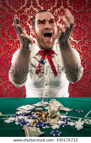 A man wearing glasses, a white shirt, and a red Texas tie sits at a blackjack table. He smiles hugely as tosses his winnings in the air./Happy Man Gets Rich at Blackjack