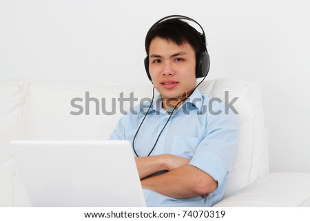 A man wearing headphones using a laptop on a sofa - stock photo
