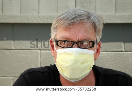 a man wears a yellow medical paper mask as he looks around to stay safe from any air born illness - stock photo
