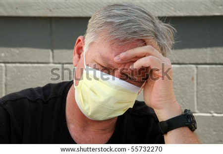 a man wears a yellow medical paper mask as he worries about how to stay safe from any air born illness - stock photo