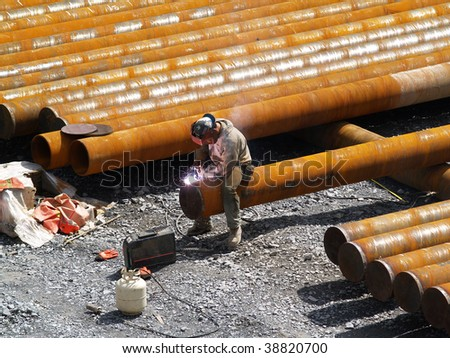 a man welding caps onto pipes - stock photo