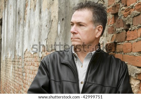 A man who appears to be deep in thought, leaning up against an old brick wall.