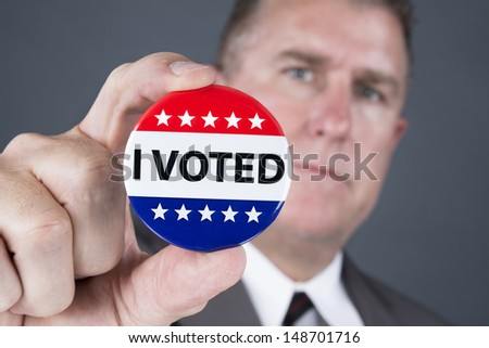 A man who voted holds up his voting badge lapel pin. - stock photo
