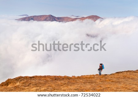 A man with a backpack is on the edge of cliffs in the mountains - stock photo
