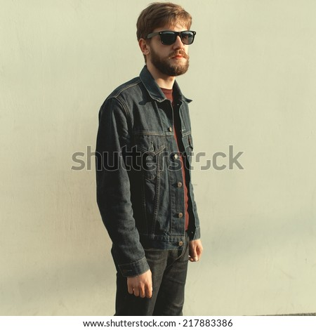 A man with a beard wearing glasses, a white wall in a sunny day - stock photo