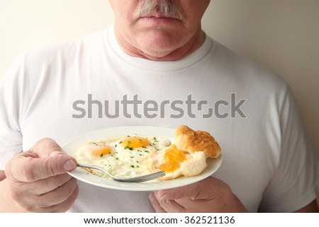 A man with a breakfast of fried eggs and a biscuit with apricot jam - stock photo
