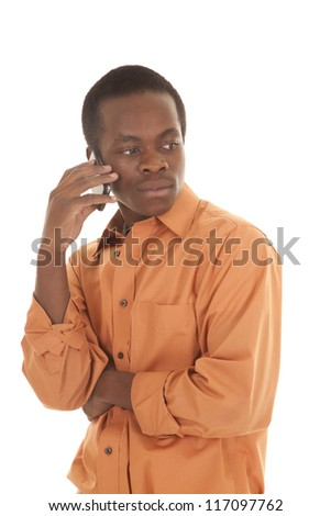 A man with a cell phone up to his ear listening with a serious expression on his face, - stock photo