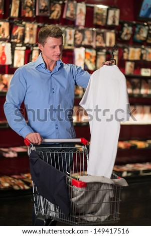 A man with a clothes in the cart in lingerie store