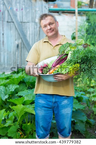 a man with a crop of vegetables in the garden - stock photo
