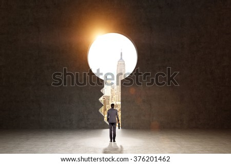 A man with a folder standing in front of a huge keyhole, New York and light seen through it. Black background. Back view.  Concept of finding the way. - stock photo