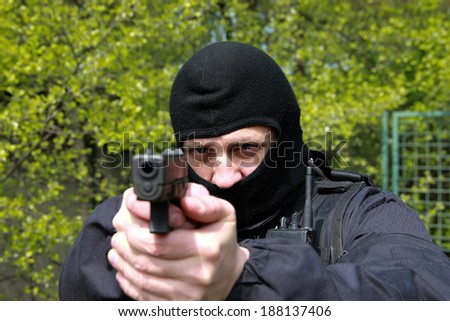 A man with a gun pointing at the target - stock photo