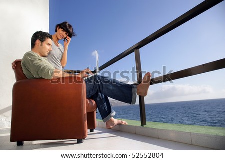 A man with a laptop computer with a smiling woman - stock photo