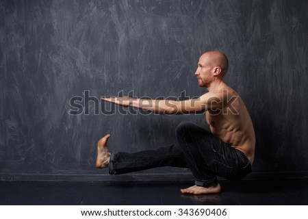 A man with a naked torso doing pistol squats on one leg on a dark background - stock photo