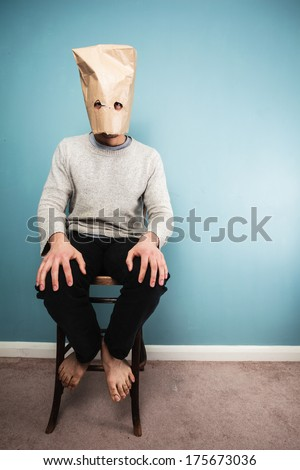 A Man with a paper bag over his head is sitting on a chair against a blue wall - stock photo