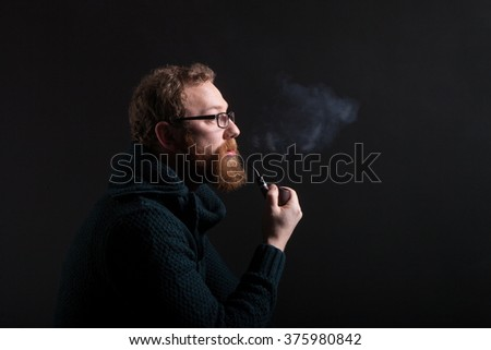 A man with a red beard with a pipe