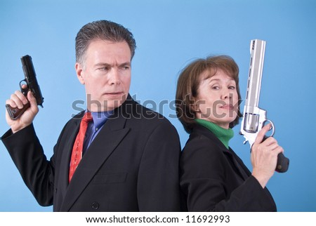 A man with a small automatic pistol in his hand looking confusedly at a woman with a very large revolver in her hand. - stock photo