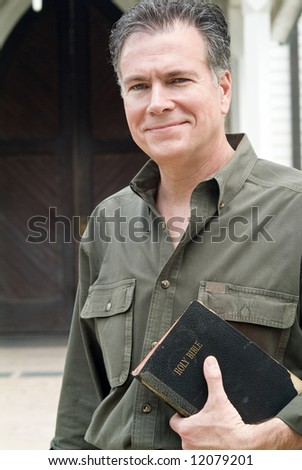 A man with a warm smile on his face, standing in front of a church, holding a bible. - stock photo
