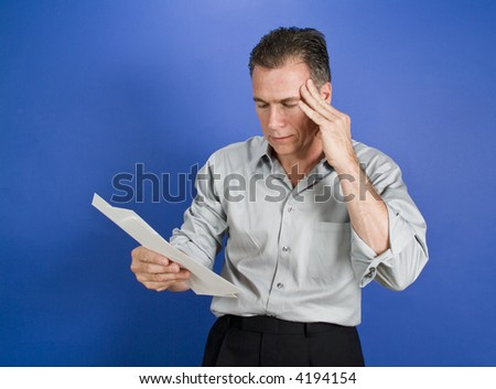 A man with a worried expression on his face holding several  envelopes in his hand. - stock photo