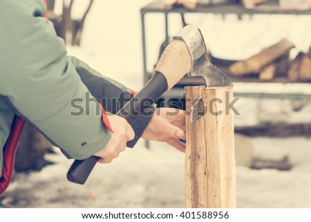 A man with an ax chopping logs in winter - stock photo