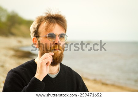 a man with an electronic cigarette at the sea - stock photo