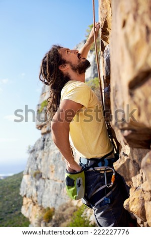 A man with dreadlocks climbing up a steep mountain with a harness and rope and looking up - stock photo