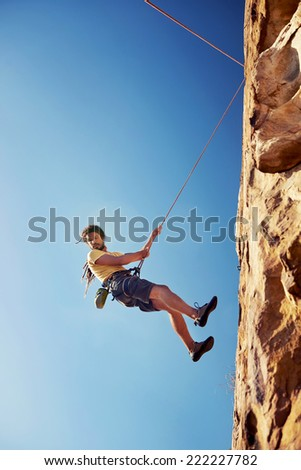 A man with dreadlocks in climbing gear rapelling down a mountain against a blue sky with rope - stock photo