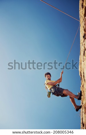 A man with dreadlocks in climbing gear repelling down a mountain against a blue sky with rope with copyspace