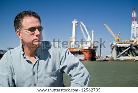 A man with drilling rigs in the background. - stock photo