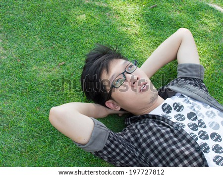 A man with glasses sleeping on grass