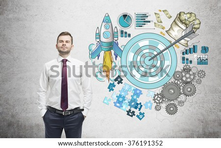 A man with hands in pockets, a picture of a target surrounded by pictures of money, rocket, charts, cogwheels and puzzles painted to the right. Concrete background. Concept of achieving a set goal. - stock photo