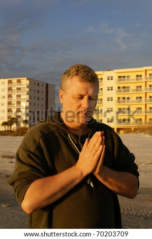 A man with his eyes closed praying at the beach with hotels behind him. - stock photo