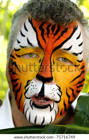 A man with his face painted like a tiger looking sad. - stock photo