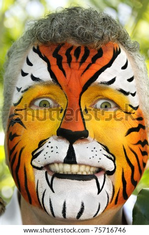 A man with his face painted to appear like a tiger, looking frightened.