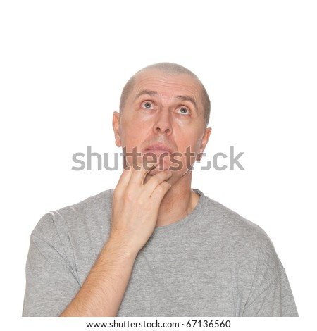 A man with his hand on his chin looks like he is thinks deeply about something. - stock photo