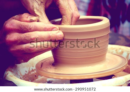 A man with his hands dub wall jug, which he sculpts out of clay on a circle - stock photo