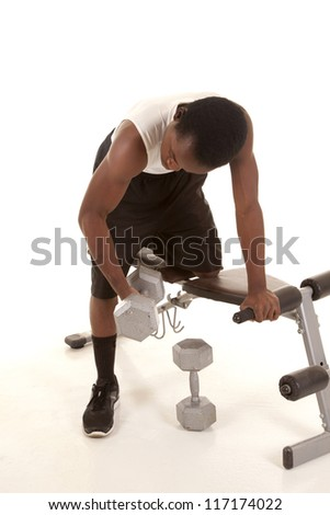 A man with his knee on a work out bench working on his bicepts.