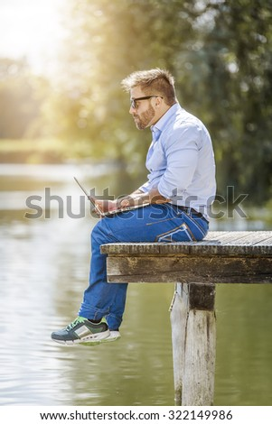 A man with his notebook is working outdoor at the lake