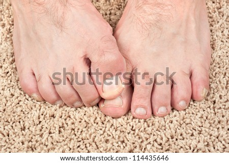 A man with itchy feet uses his big toe to scratch his other foot. Good for grooming inferences as well. - stock photo
