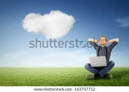 a man with laptop is relaxing on a green meadow with a cloud in the sky in the background