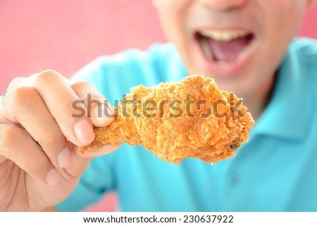 A man with opening mouth about to eat deep fried chicken leg or drumstick