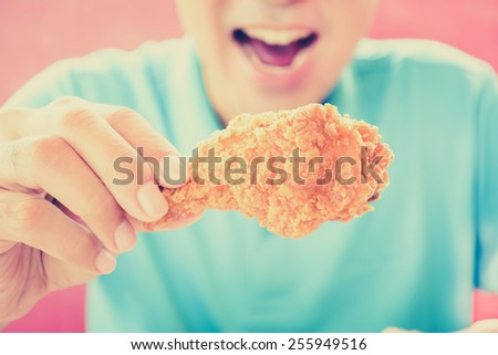 A man with opening mouth about to eat deep fried chicken leg or drumstick - vintage style color effect - stock photo